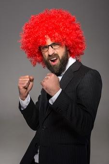 Homme barbu en costume et une perruque rouge.