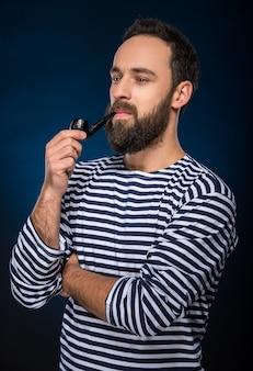 Un homme barbu en costume rayé fume la pipe.