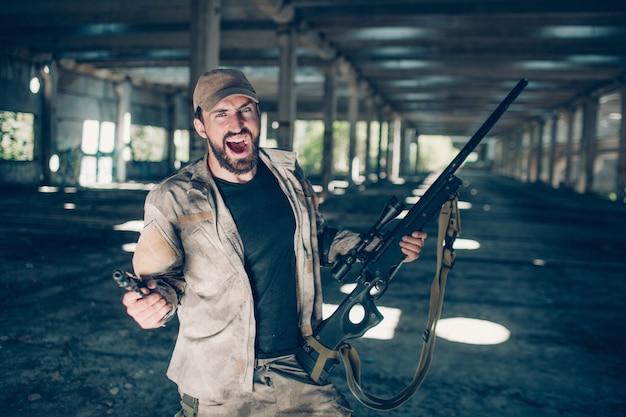 Un homme barbu courageux et intrépide est debout et hurle. il est fou. guy tient un fusil dans la main gauche et un pistolet dans la droite. l'homme est fou.