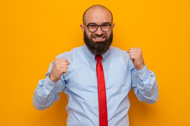 Homme barbu en cravate rouge et chemise bleue portant des lunettes à poings serrés heureux et excités