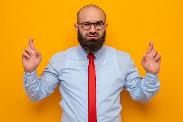 Homme barbu en cravate rouge et chemise bleue portant des lunettes à la recherche de sourire et un clin de souhait désirable croisant les doigts