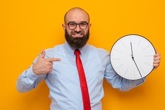 Homme barbu en cravate rouge et chemise bleue portant des lunettes tenant une horloge pointée avec l'index souriant joyeusement