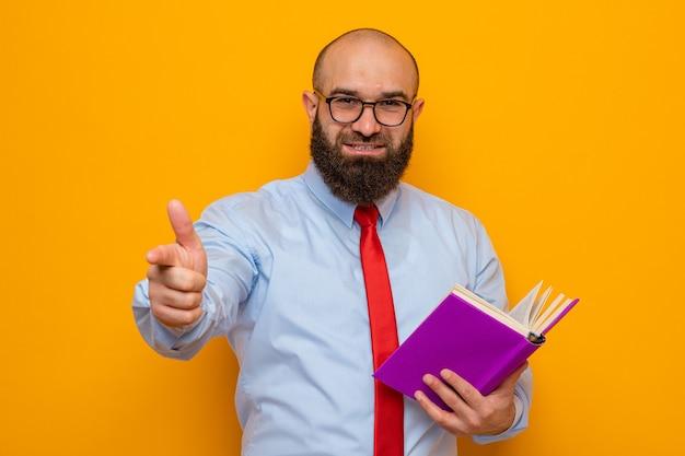 Homme barbu en cravate rouge et chemise bleue portant des lunettes tenant un livre pointant avec l'index à l'avant