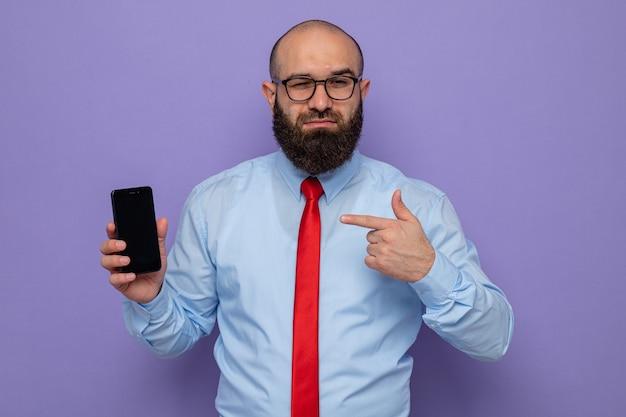 Homme barbu en cravate rouge et chemise bleue portant des lunettes tenant un smartphone pointant avec l'index à la confiance en souriant