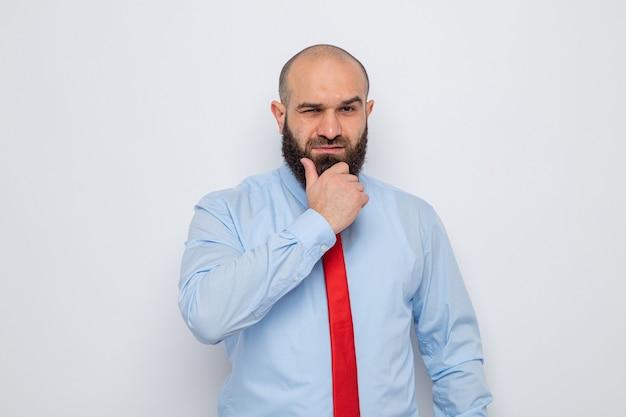 Homme barbu en cravate rouge et chemise bleue regardant avec han sur son menton avec une expression pensive pensant