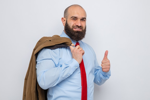 Homme barbu en cravate rouge et chemise bleue tenant un costume sur son épaule à sourire joyeusement montrant le pouce vers le haut