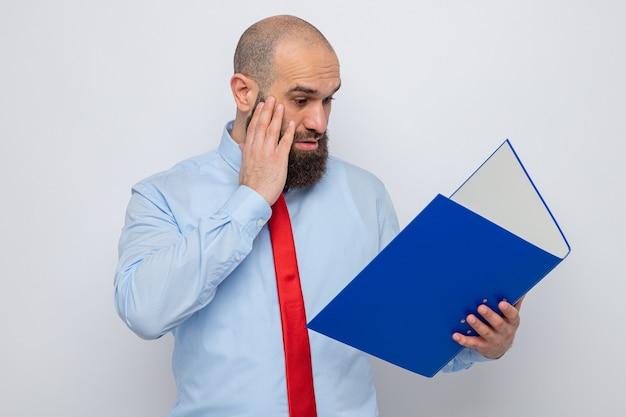 Homme barbu en cravate rouge et chemise bleue tenant un dossier de bureau le regardant confus et surpris debout sur fond blanc