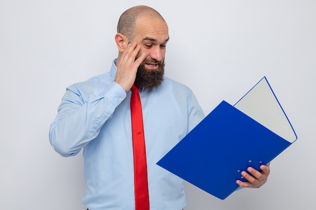 Homme barbu en cravate rouge et chemise bleue tenant un dossier de bureau en le regardant étonné et surpris debout sur fond blanc