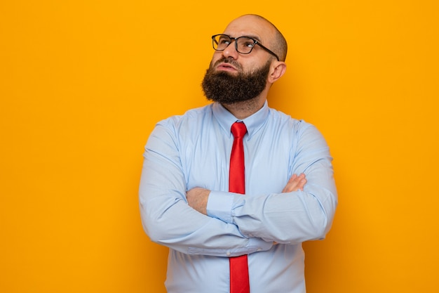 Homme barbu en cravate rouge et chemise portant des lunettes en levant avec une expression pensive avec les bras croisés