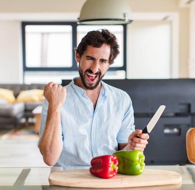 Homme barbu criant agressivement avec une expression de colère ou avec les poings serrés célébrant le succès