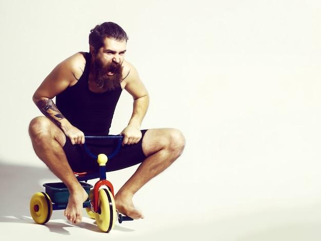 Homme barbu criant assis sur un jouet vélo coloré
