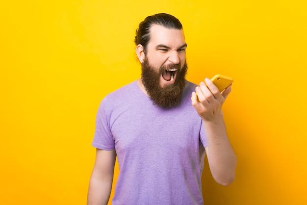 L'homme barbu crie au téléphone qu'il tient.