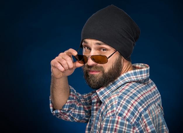 Homme barbu dans un bonnet et des lunettes regarde la caméra