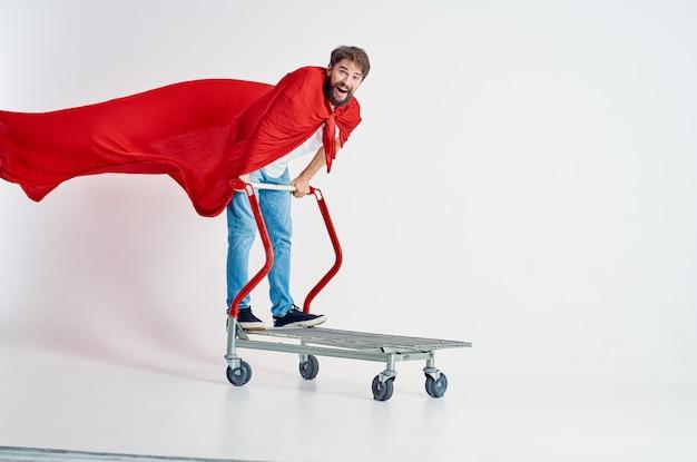 Homme barbu dans une cape rouge transport dans une boîte fond isolé