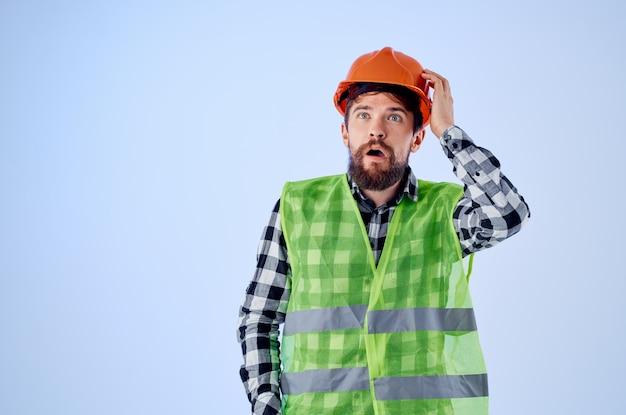 Homme barbu dans un casque de protection orange fond isolé professionnel