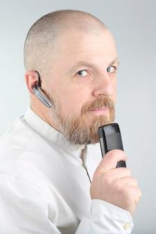 Homme barbu dans une chemise légère avec un téléphone portable et bluetooth dans son oreille