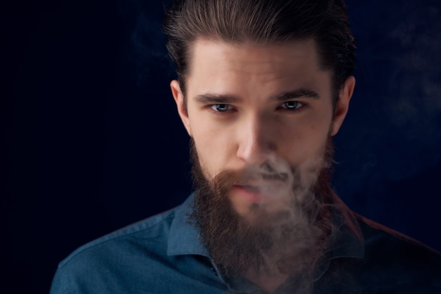 Homme barbu dans une chemise noire nuages de fumée fond sombre