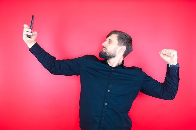 Un homme barbu dans une chemise noire pose devant la caméra de son téléphone en prenant un selfie