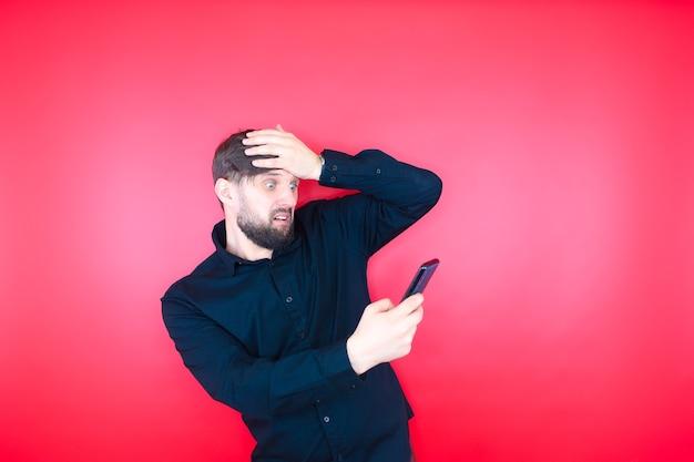 Un homme barbu dans une chemise noire tient un téléphone dans sa main, tenant sa tête. le barbu est sous le choc