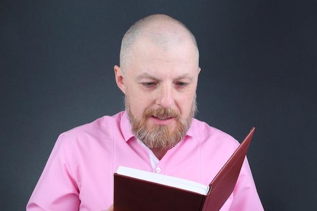 Homme barbu dans une chemise rose en lisant un livre