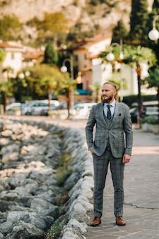Un homme barbu dans un costume trois pièces gris strict se dresse dans le contexte des alpes près de torbole, italie