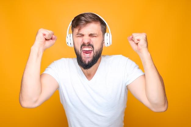 Homme barbu dans des écouteurs blancs écoutant de la musique énergique et chantant avec émotion.