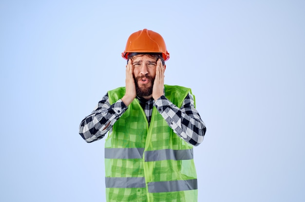 Homme barbu dans le fond bleu professionnel de construction de casque orange