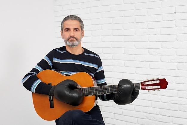 Homme barbu dans des gants de boxe, jouer de la guitare.