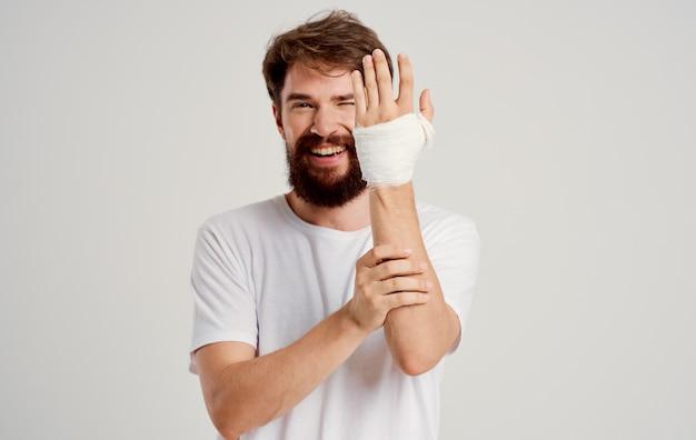 Homme barbu dans un t-shirt blanc avec une main bandée posant sur fond clair