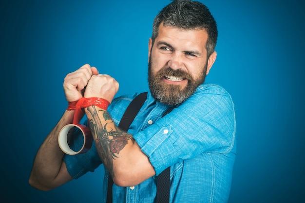 Homme barbu dans des vêtements décontractés avec du ruban isolant rouge essayant de déverrouiller les mains insatisfait