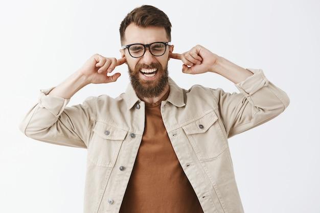 Homme barbu dérangé en colère dans des verres posant contre le mur blanc