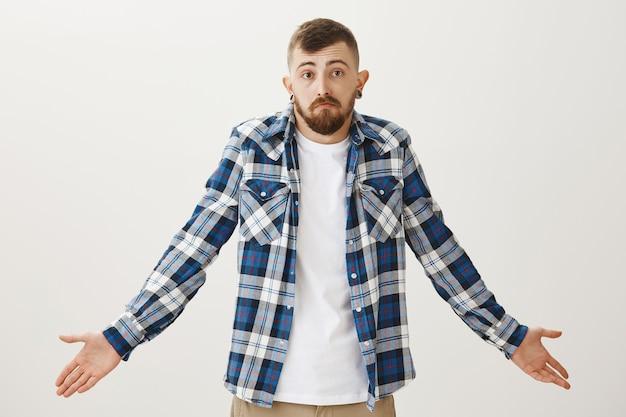 Homme barbu désemparé haussant les épaules et l'air indécis, je ne sais rien