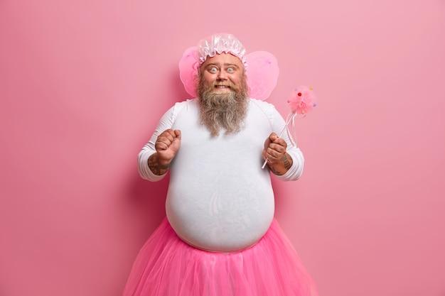 Un homme barbu dodu a l'image d'une fée magique, serre le poing, heureux de sa capacité à faire disparaître les choses, fait semblant d'être un être surnaturel, joue avec les enfants à la fête