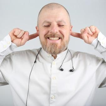 Homme barbu avec les doigts dans les oreilles au lieu d'écouteurs