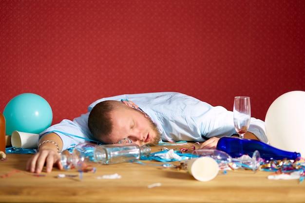 Homme barbu dormant à table dans une chambre en désordre après l'enterrement de vie de garçon, homme fatigué après la fête à la maison