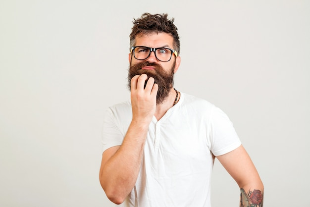 Homme barbu doutant de nouvelle idée sur fond blanc. hipster barbu pensant à un nouveau plan de démarrage.