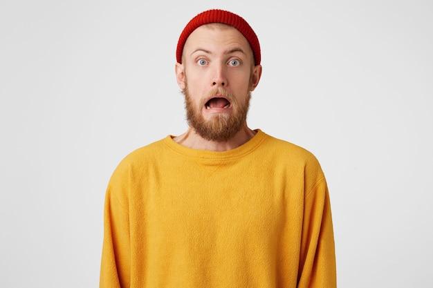 Un homme barbu effrayé aux yeux bleus regarde avec une grimace d'horreur