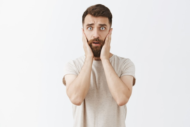 Homme barbu effrayé paniqué posant contre le mur blanc