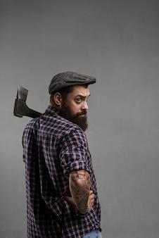 Un homme barbu élégant en casquette et chemise avec une hache sur l'épaule regarde la caméra. beau forestier tourné en studio. mâle brutal avec tatouage.