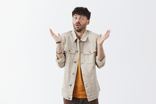 Homme barbu élégant et désemparé posant contre le mur blanc