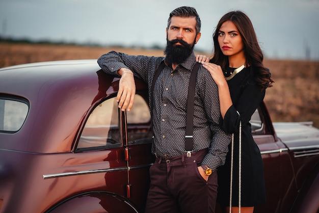 Homme barbu élégant en pantalon classique avec bretelles embrasse une jeune fille brune dans une robe noire près d'une voiture rétro au coucher du soleil
