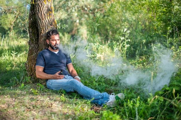 Un homme barbu élégant vapote et libère un nuage de vapeur