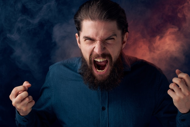 Homme barbu émotionnel en colère look chemise fumée en arrière-plan.