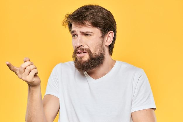 Homme barbu émotions gestes avec mains expression du visage t-shirt blanc espace jaune