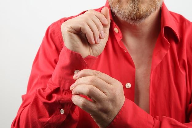 Homme barbu enlève sa chemise rouge déshabillée