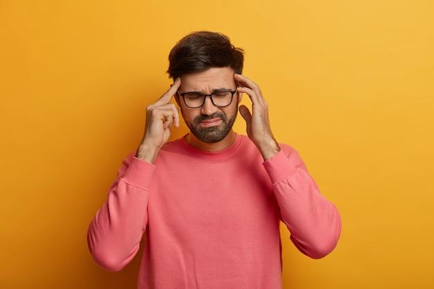 Un homme barbu épuisé souffre de maux de tête insupportables