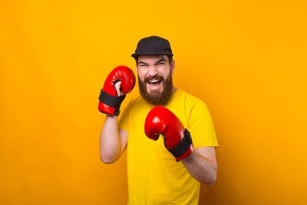 Un homme barbu est assis sur une boîte pose avec des gants de combat sur près d'un mur jaune