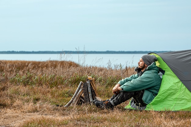 Un homme barbu est assis, campant dans une tente, en toile de fond la nature et le lac. voyages, tourisme, camping.