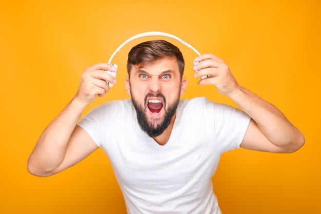 Un homme barbu étire le casque dans différentes directions et crie fort dans la caméra.