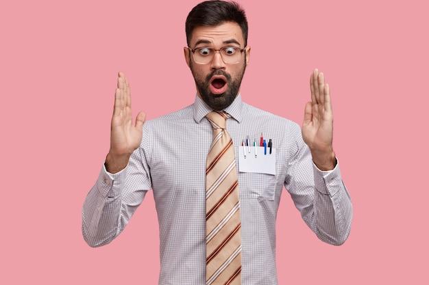 Un homme barbu étonné choqué fait des gestes actifs, montre quelque chose de très énorme, a surpris l'expression, porte une chemise formelle avec une cravate